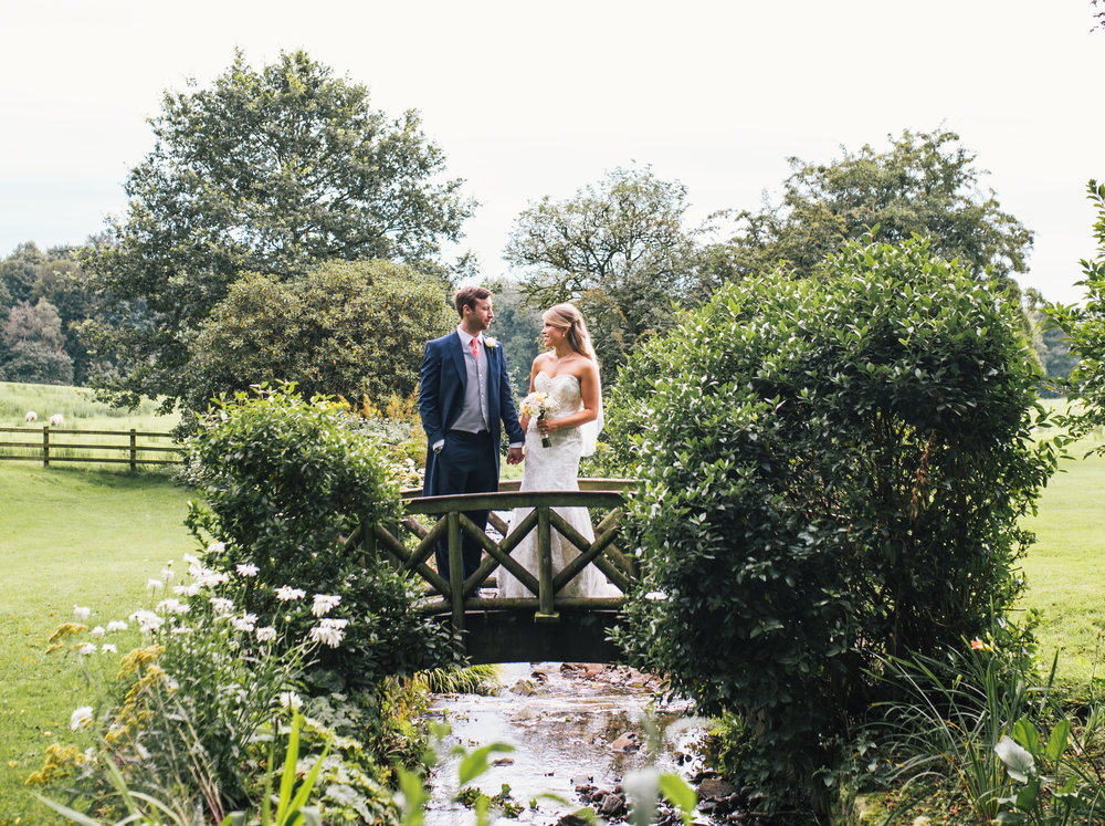 Creative wedding photography of the bride and groom on the bridge- Browsholme Hall