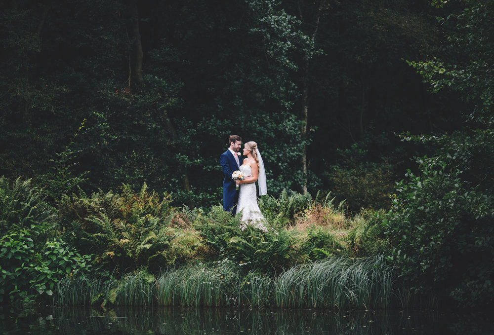 The bride and groom in the distance surrounded by the green trees at Browsholme Hall