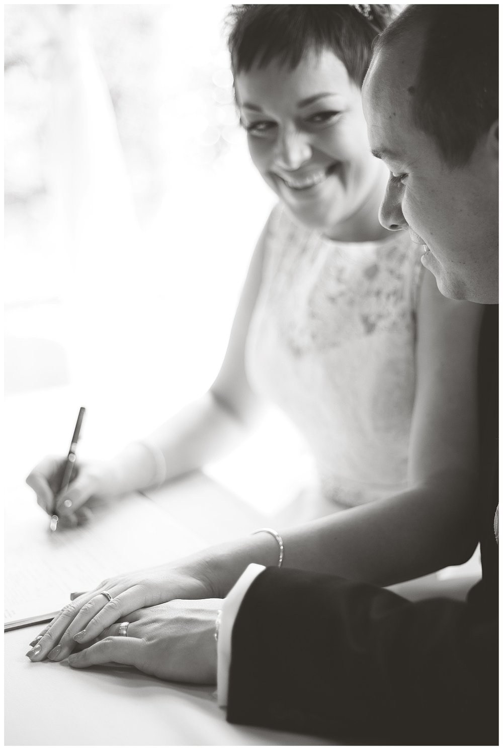Bride and groom hand in hand as they sign the book- tyal lodge wedding in Cheshire photography