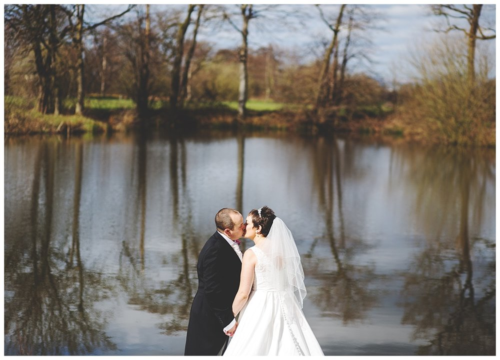 The bride and groom kissing by the pond at styal lodge wedding in Cheshire