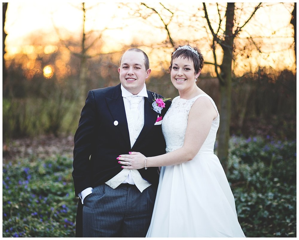The bride and groom surrounded by trees as the sun sets at styal lodge