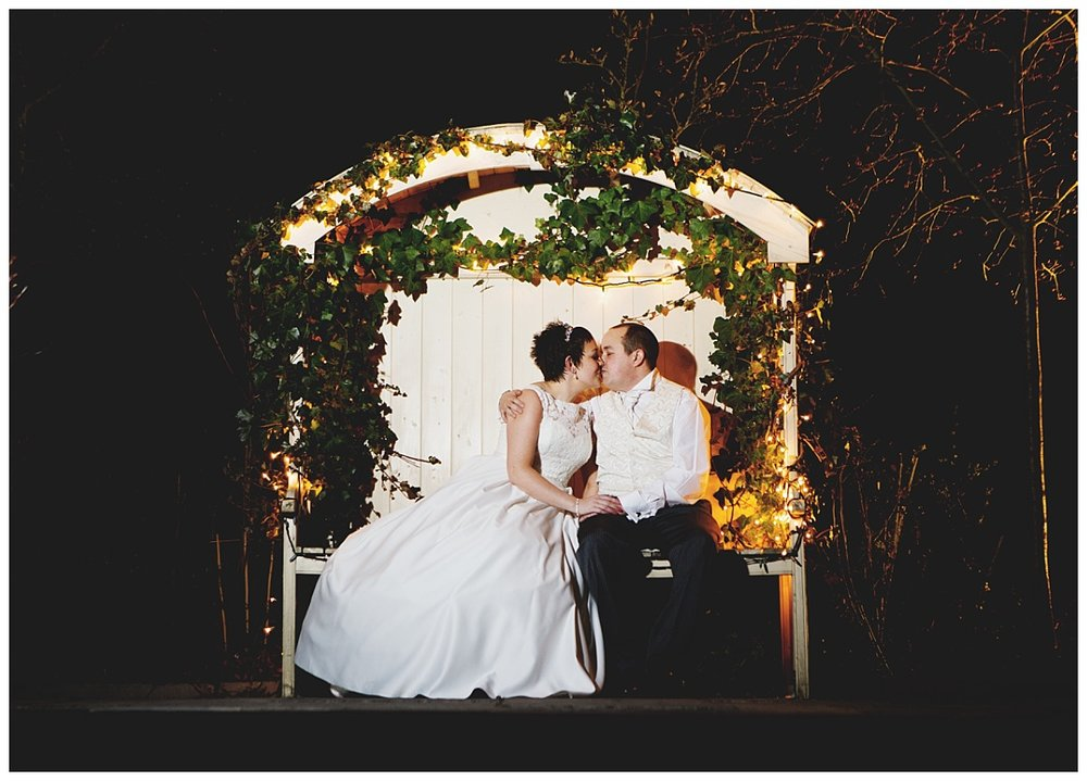 The bride and groom kissing sat on a bench at night- cheshire wedding photography, creative