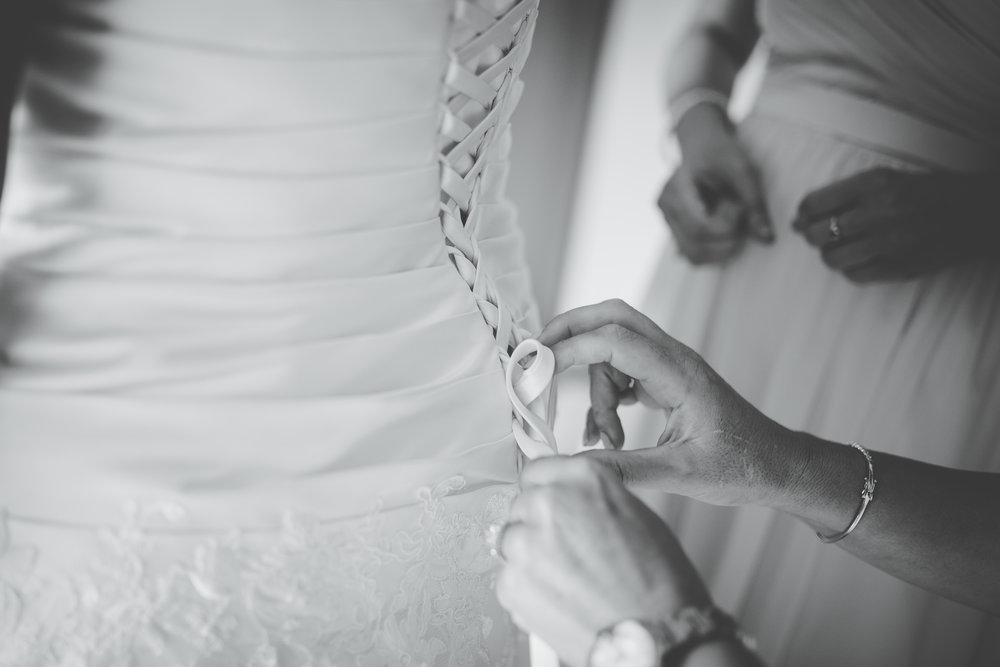 Black and white photograph of the bride having her dress tied- Creative wedding photography