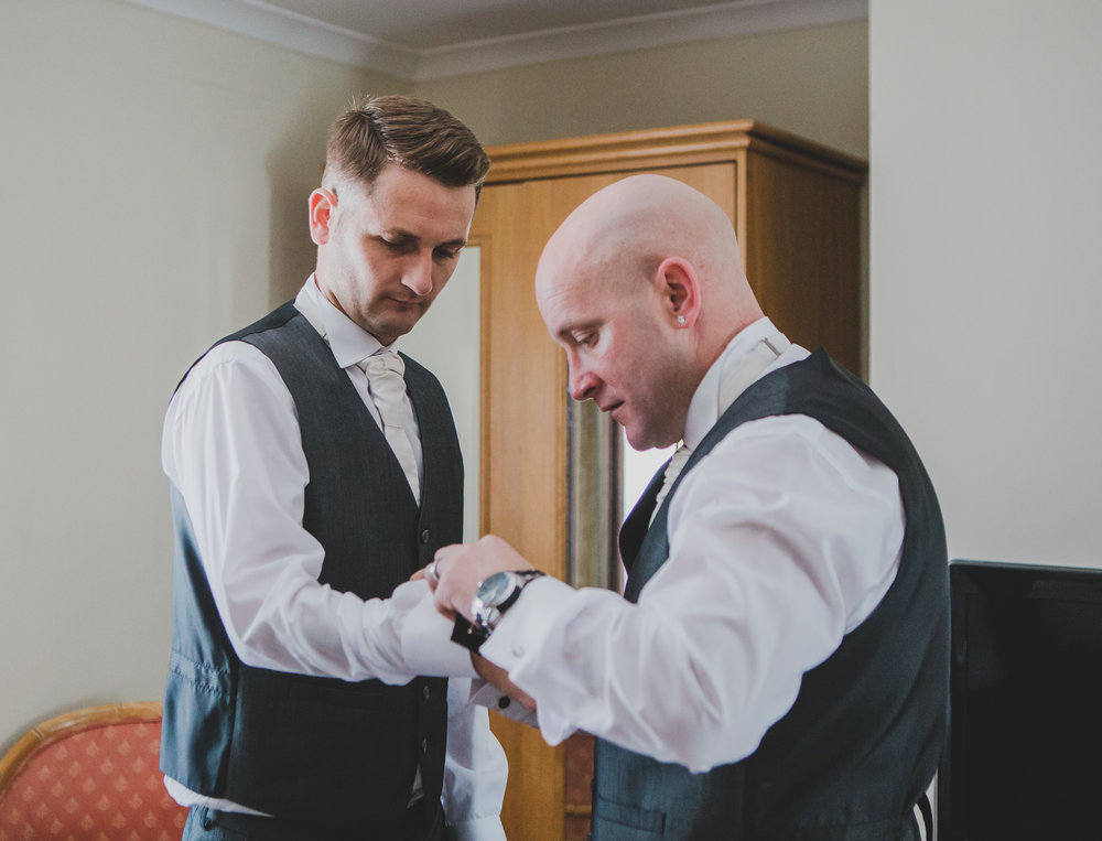 Help is needed to put the cuff links on the groom - Documentary photograph lancashire