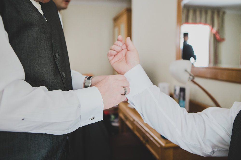 The cuff links being put on the groom- Documentary styled wedding photography