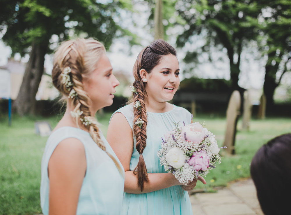 Documentary wedding photography of th bridesmaids looking at the bride outside of Beeston Manor
