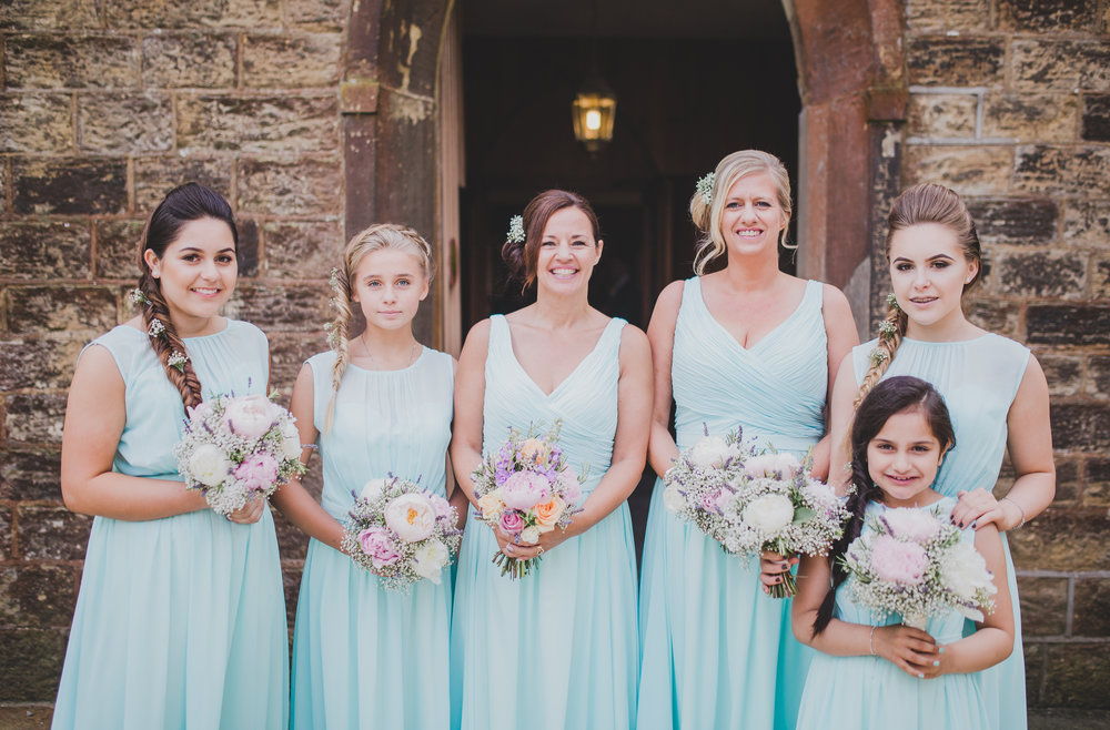 Bridesmaids all in a line outside of Beeston Manor, Lancashire