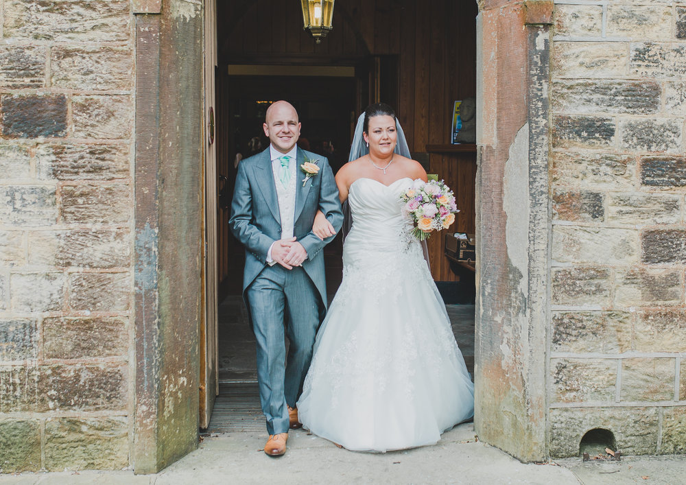 The bride and groom walking out of Beeston Manor as Mr and Mrs