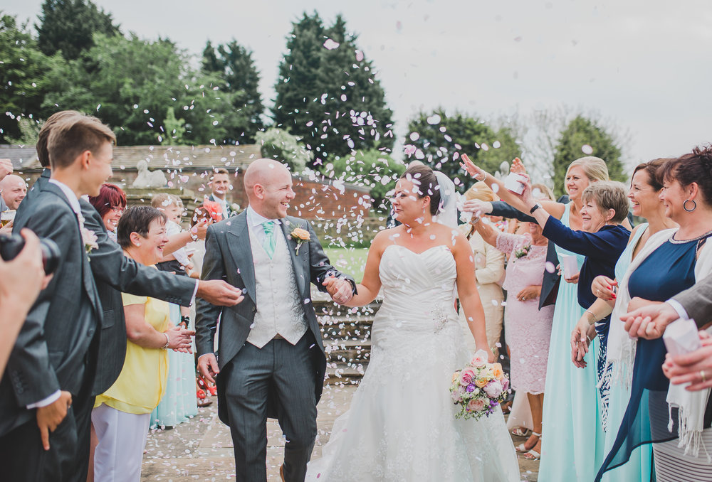 Bride and groom walking through confetti- Creative wedding photography