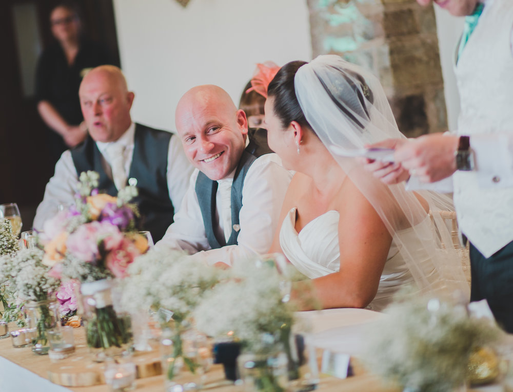 Smiles from the bride and groom during the wedding speeches- Lancashire wedding photographer