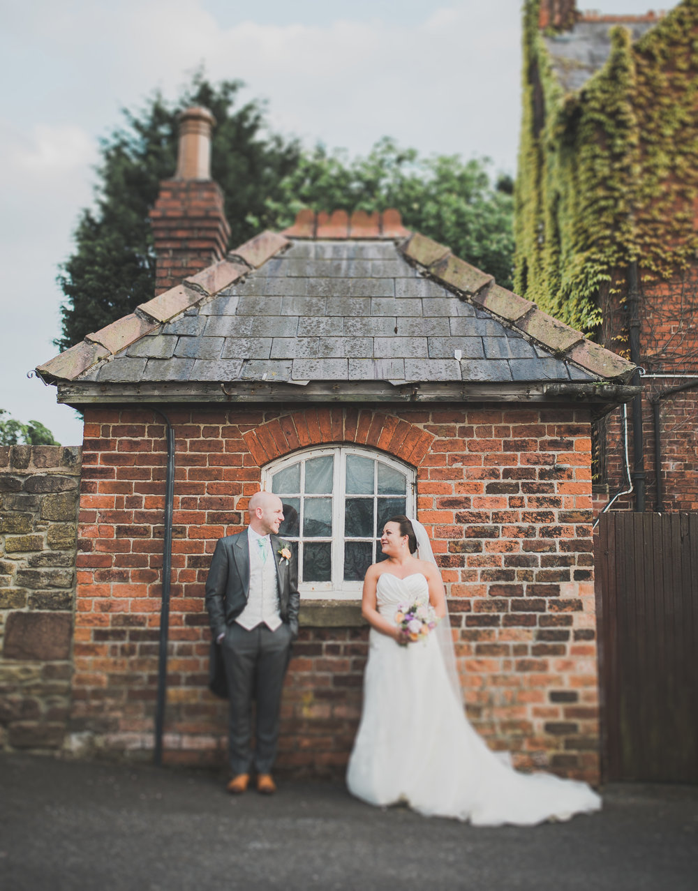 Bride and groom stood across one another at a window at Beeston Manor in Preston, lancashire