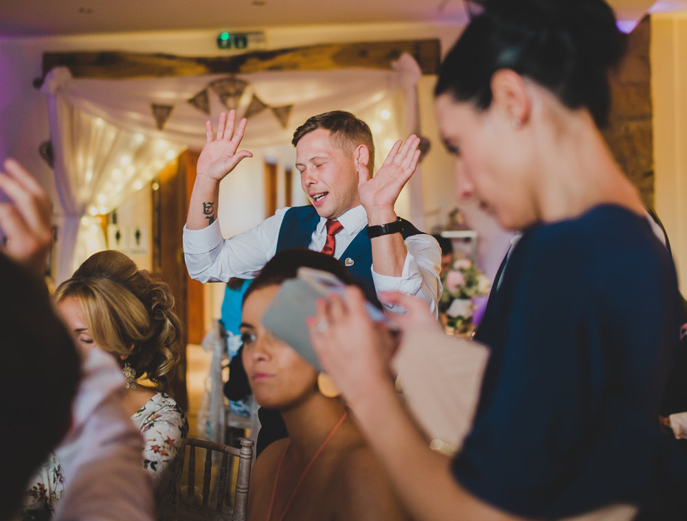 Wedding guests making their way to the dance floor dancing- Creative wedding photography in lancashire