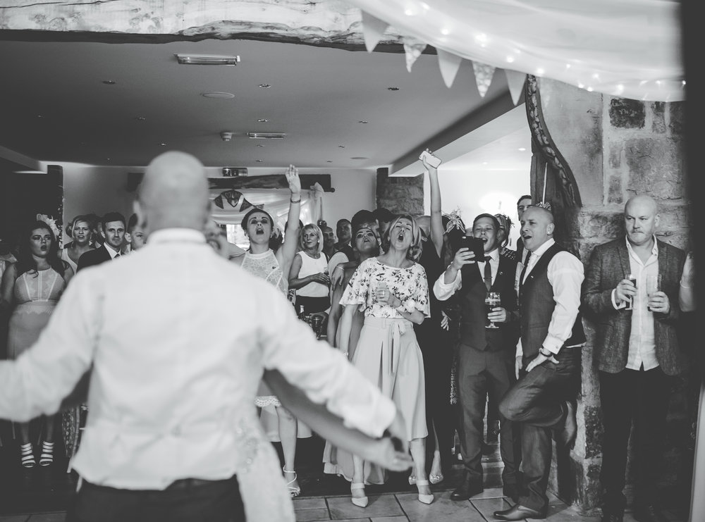 Black and white photograph of the bride and groom dancing- Creative wedding photography at Beeston Manor