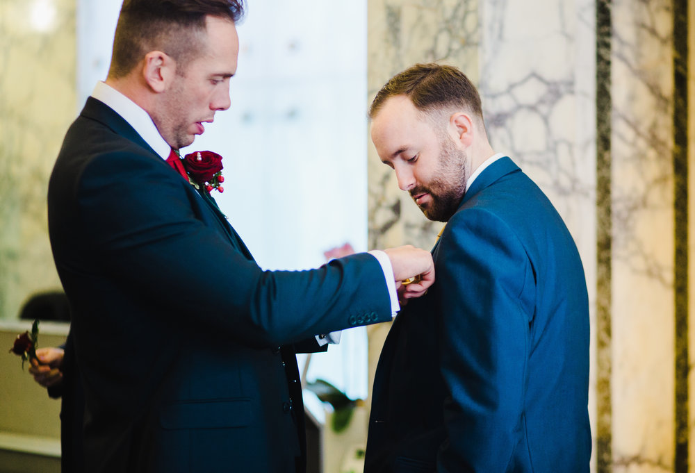 The best man putting the button hole flower of the groom- Liver Building Weddings