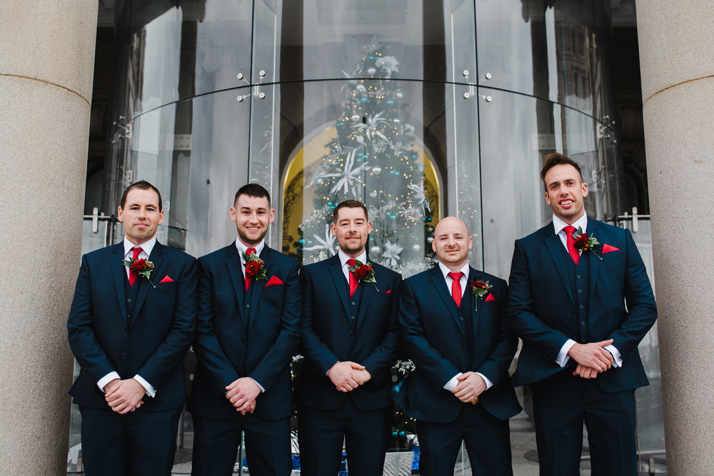 The groom and groomsmen stood infront of the Christmas tree at Liver Building- Winter themed wedding