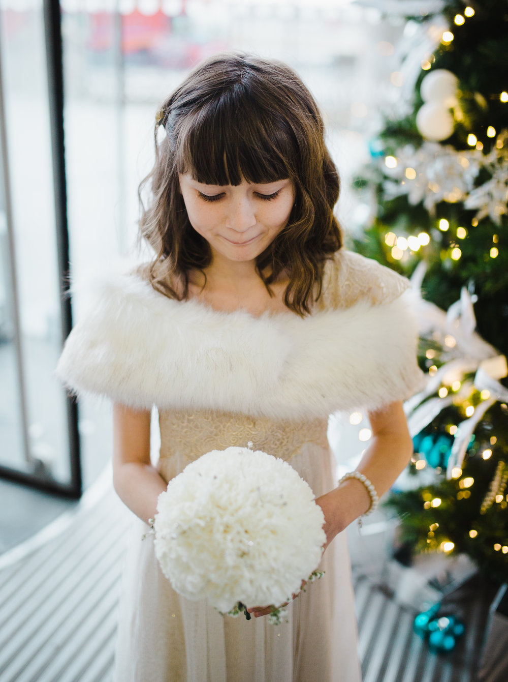 The young bridesmaid holding the flower bouquet- Christmas themed wedding at the liver building