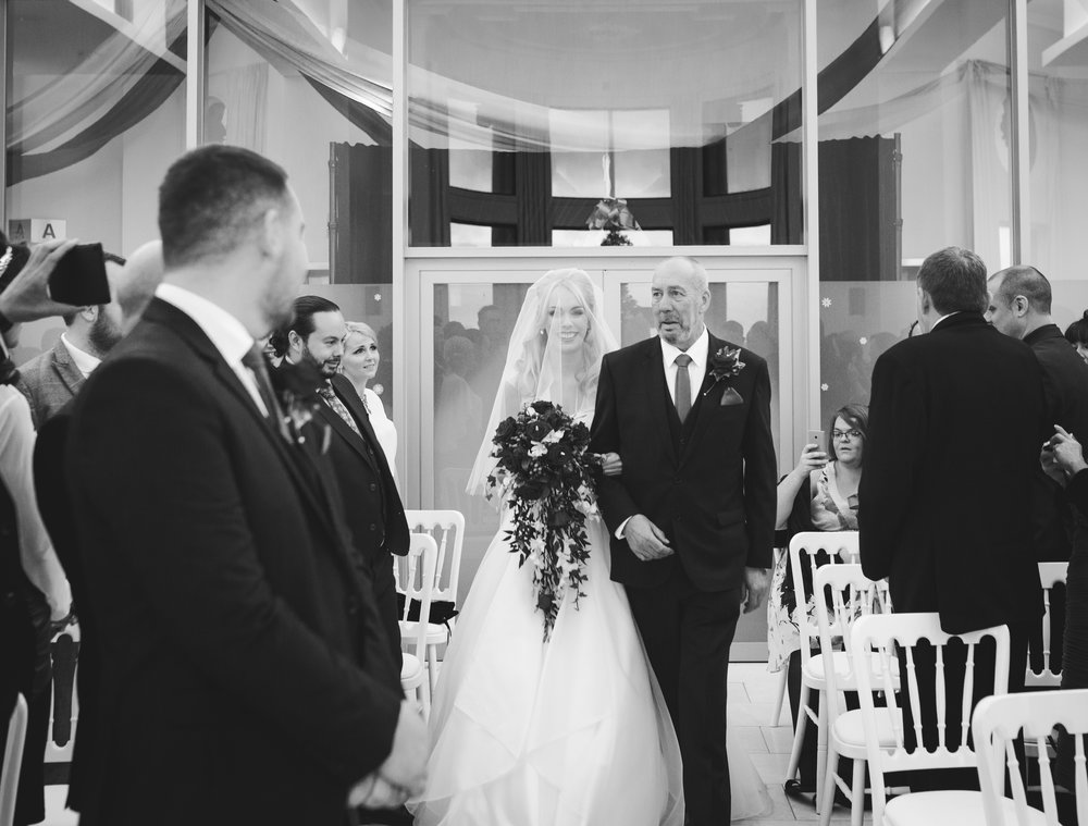 Documentary photograph of the bride and father walking down the aisle.- North west photographer