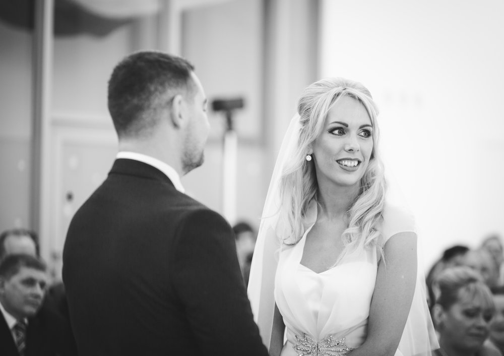 Black and white photograph of the bride ad groom giving one another the rings- Documentary wedding photography