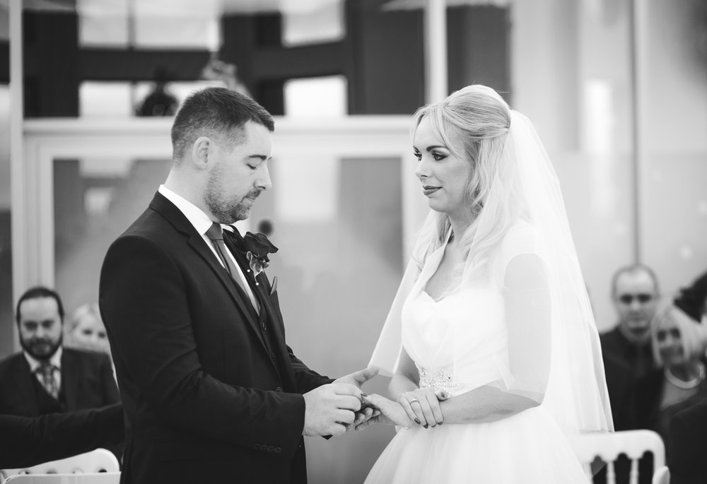 Black and white photograph of the groom placing the ring of his brides finger- Creative wedding photography