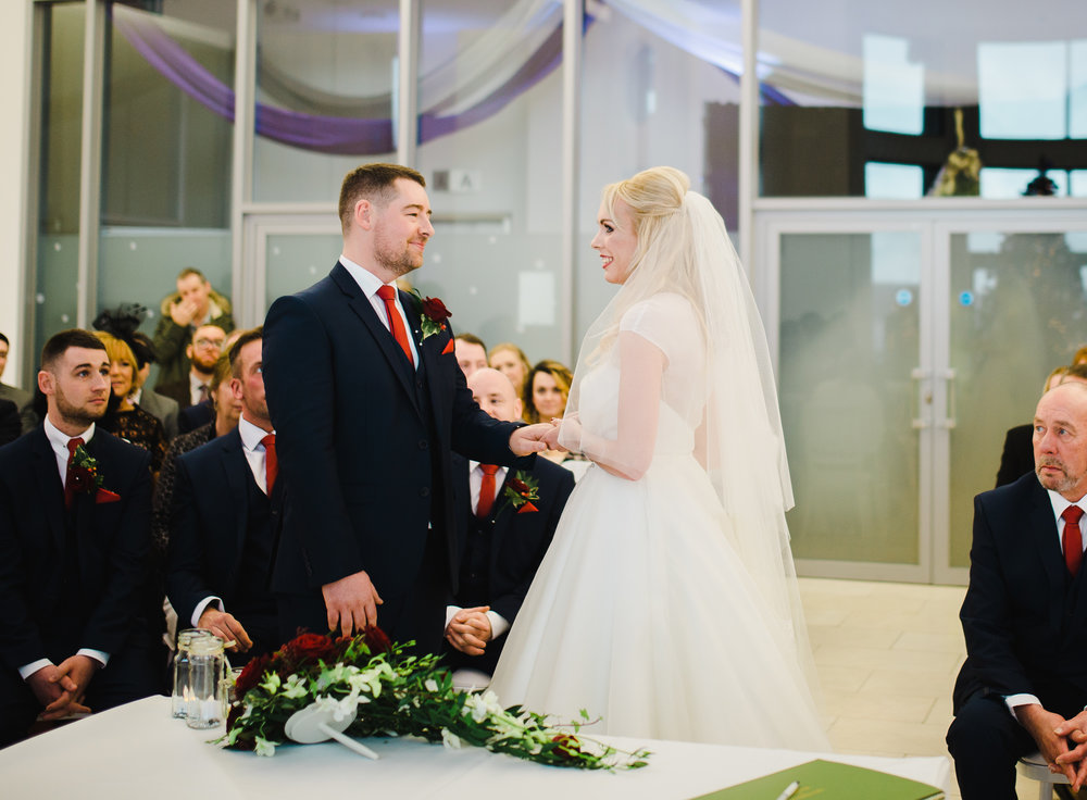 The bride placing the wedding ring on her grooms finger- Documentary wedding photography at the Liver building