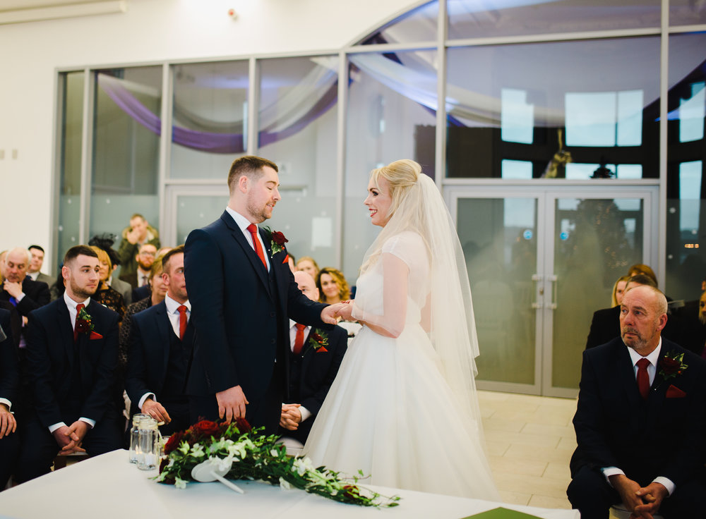 The bride and groom looking into one another eyes as they say their vows- Relaxed christmas themed wedding in the north west