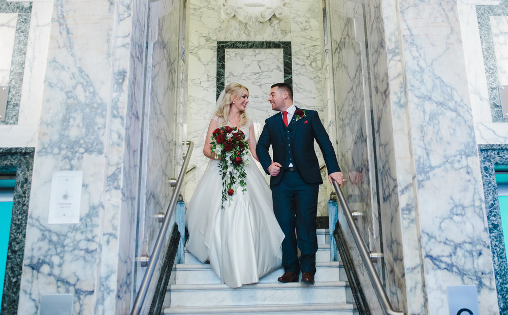 Bride and groom walking down the stairs as Mr and Mrs- Creative wedding photography in he north west