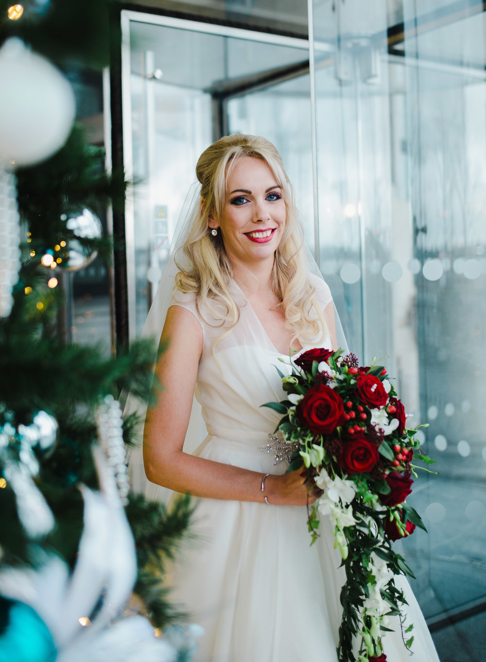 Portrait of the bride with her flower bouquet next to the christmas tree at the liver building- Christmas themed wedding