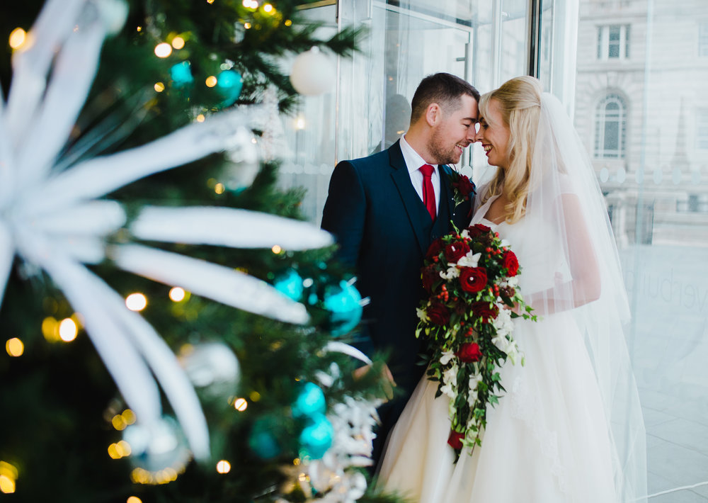 The brides and groom kissing next to the christmas tree at liver buildings in liverpool- creative wedding photography