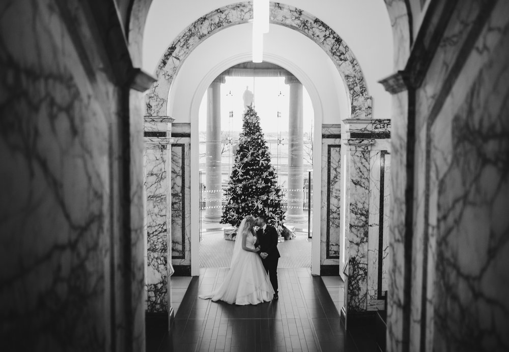 The bride and groom stood near the big christmas tree at Liver buildings in liverpool- christmas themed wedding