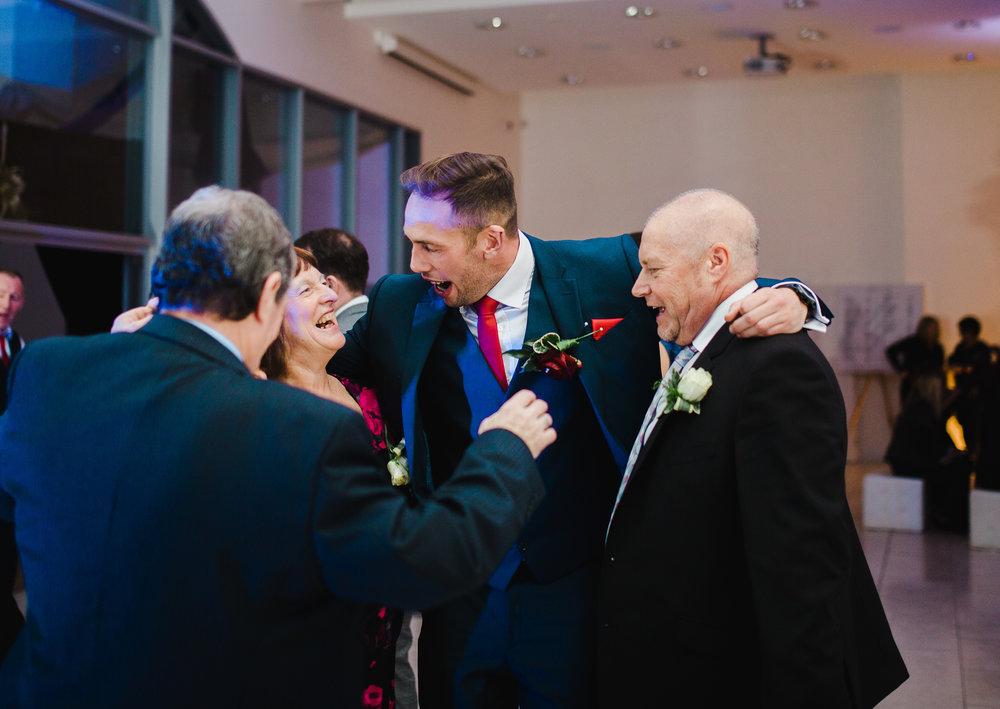 big smiles from the groom and groomsmen on the dance floor- creative wedding photography
