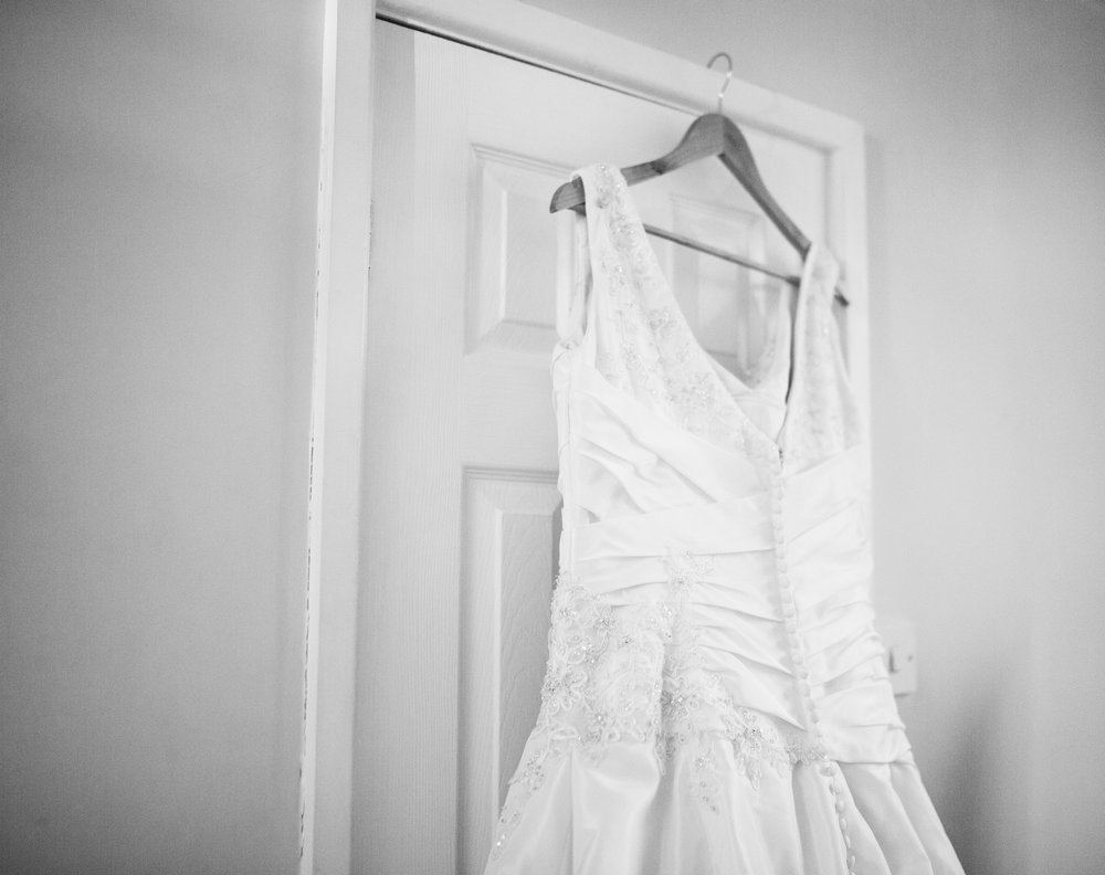 The brides wedding dress hung up on the door frame- Ribble Valley wedding