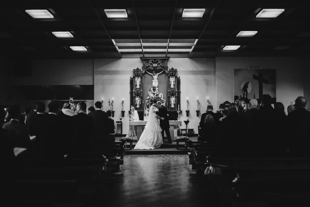 Black and white photography of the bride and groom kissing at the alter- Creative wedding photography in the ribble valley