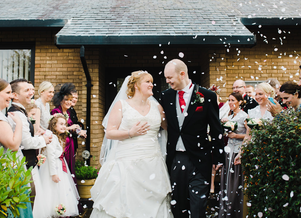 Lots and lots of confetti throwing for the bride and groom at Spread Eagle Wedding venue