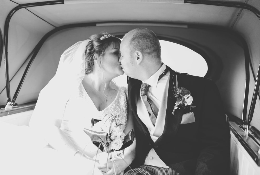 Black and white photograph of the bride and groom kissing in the old vintage wedding car- Creative wedding photography Lancashire