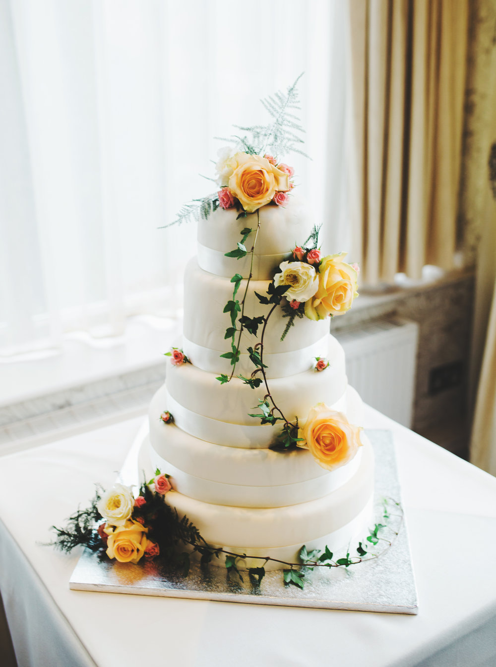 The wedding cake topped with orange and yellow flowera- Ribble Valley wedding photographer