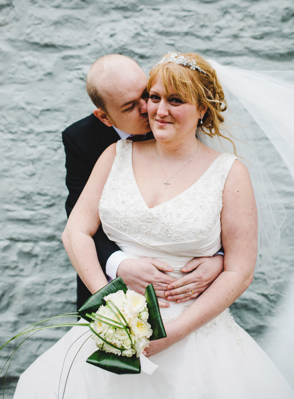 The bride sat on the groom as he kisses her cheek- Creative wedding photography in lancashire