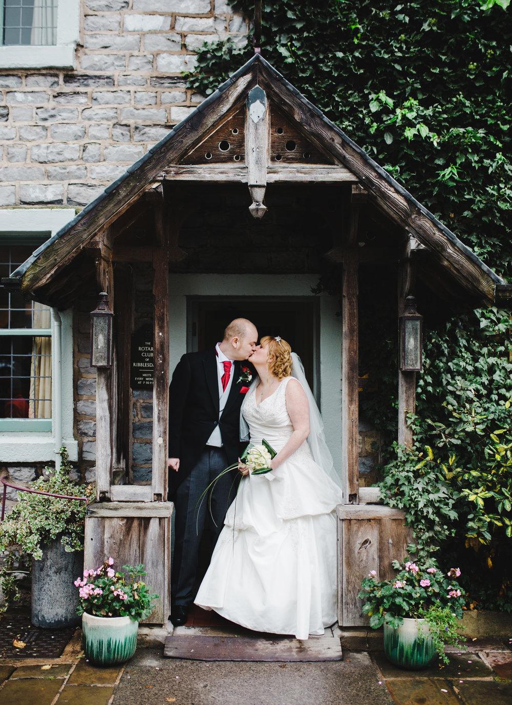 The bride and groom kissing in the door way of Spread Eagle Wedding venue