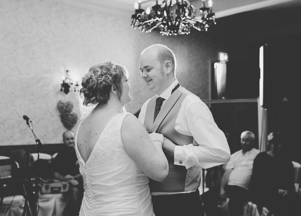 Bride and groom holding hands on the dance floor- Creative wedding photography in lancashire