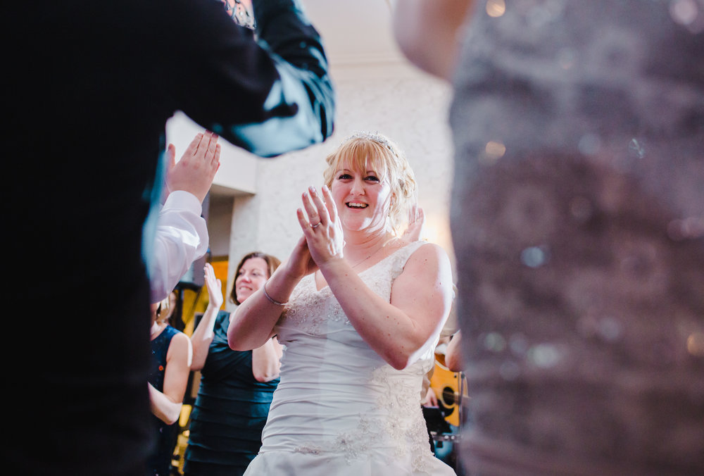 The bride through many wedding guests on the dancefloor- Lancashire wedding photography