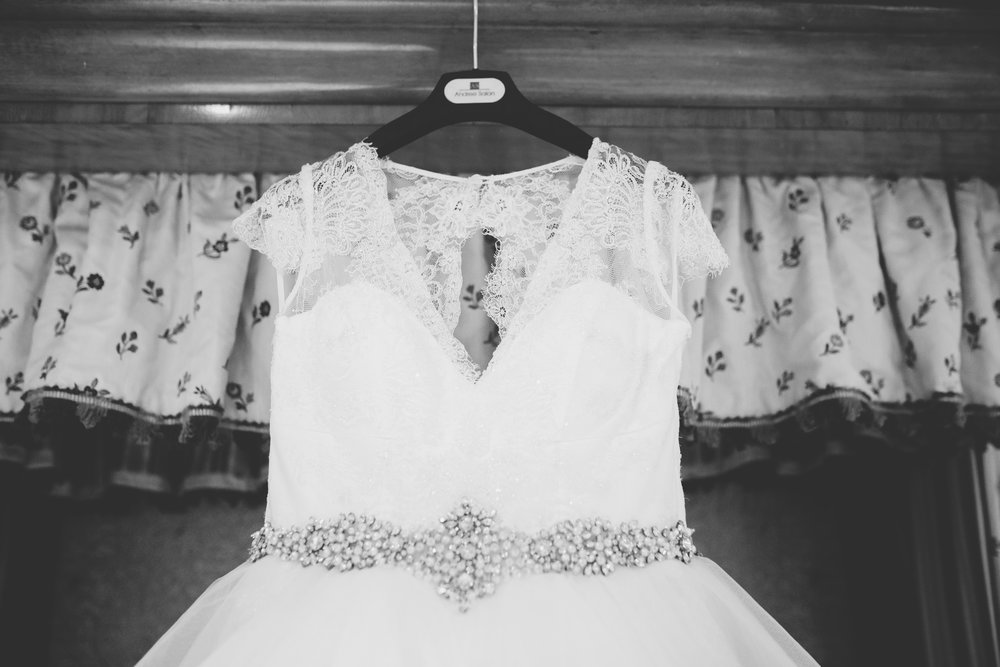 The brides wedding gown hung on the door, black and white photograph- West Yorkshire wedding at Houldsworth House