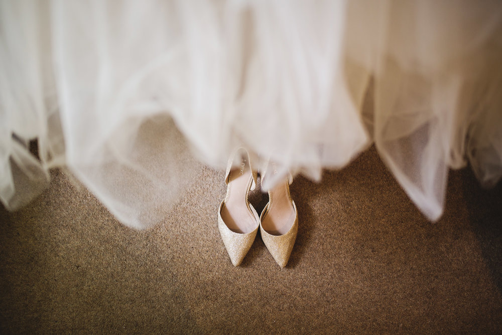 the brides shoes placed under the wedding dress- relaxed wedding venue of Houldsworth House