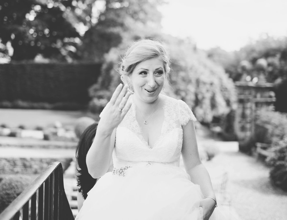 Black and white photograph of the bride tearing up as she walks outside of the Houldsworth House, west yorkshire- Lovely relaxed wedding photography
