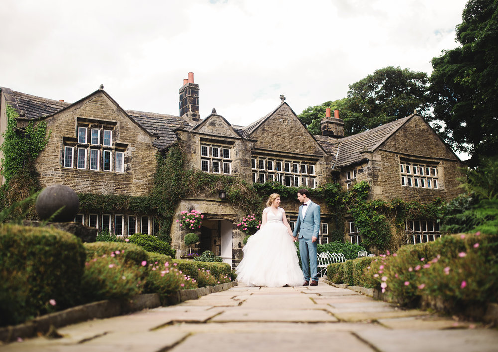 The bride and groom stood outside of the Houldsworth House in west yorkshire- Creative wedding photography in north west