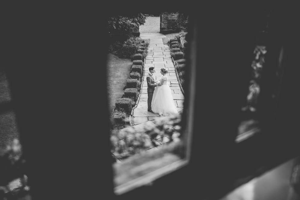 The bride and groom stood outside of Houldsworth House, photography taken from upstairs window- creative wedding photography in black and white