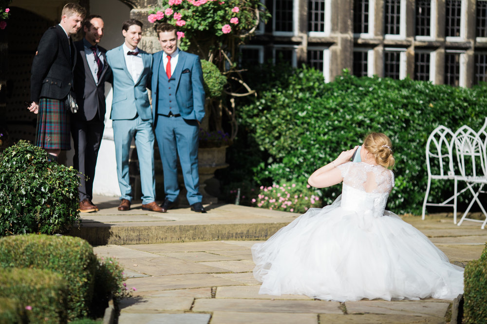 The bride taking a photograph of her wedding guests- documentary wedding photography