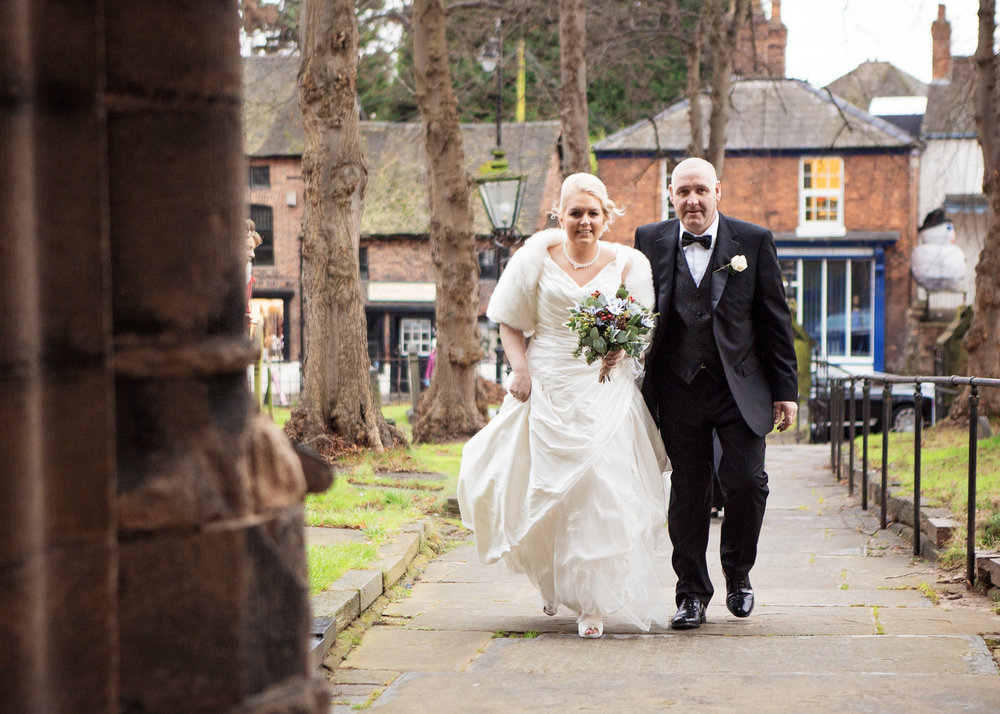 The bride and her father walking up to the church in Cheshire - documentary wedding photography