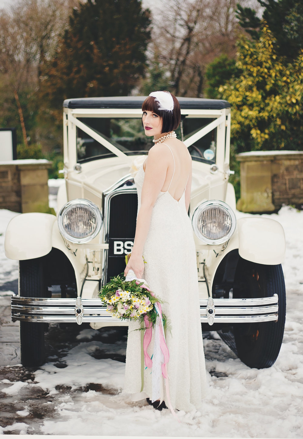The bride stood infront of the wedding car with flowers her hand- Lancashire 1920 themed wedding, creative photography
