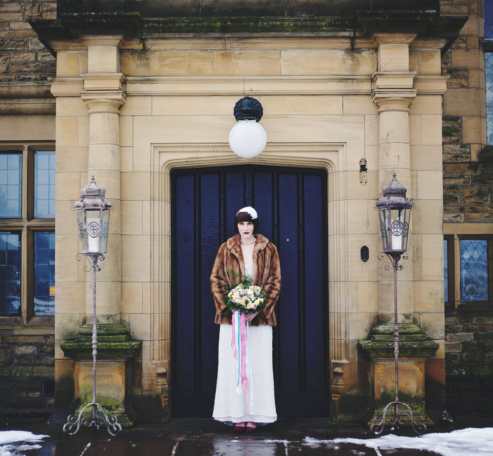 The bride stood at the blue door at Haworth Art Gallery- Creative 1920 wedding photography