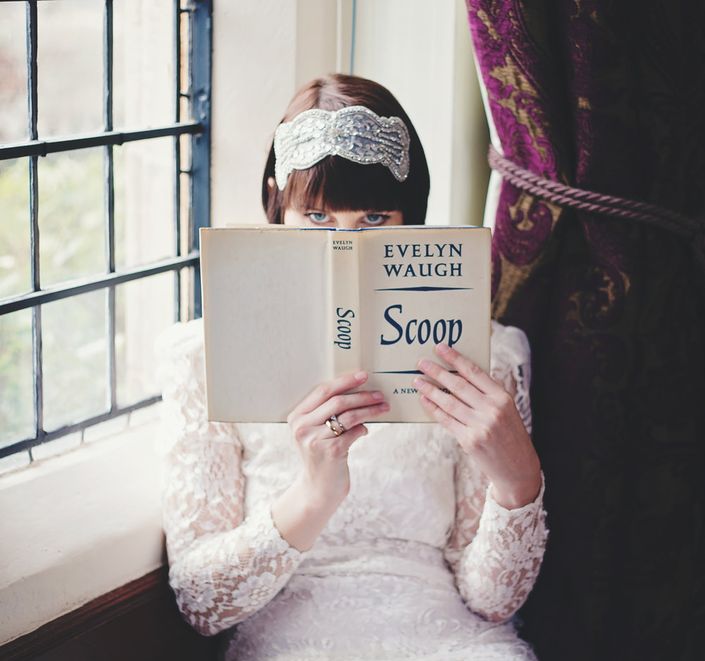 The bride sat by the window as she hides behind the book- Haworth Art Gallery for a wedding venue