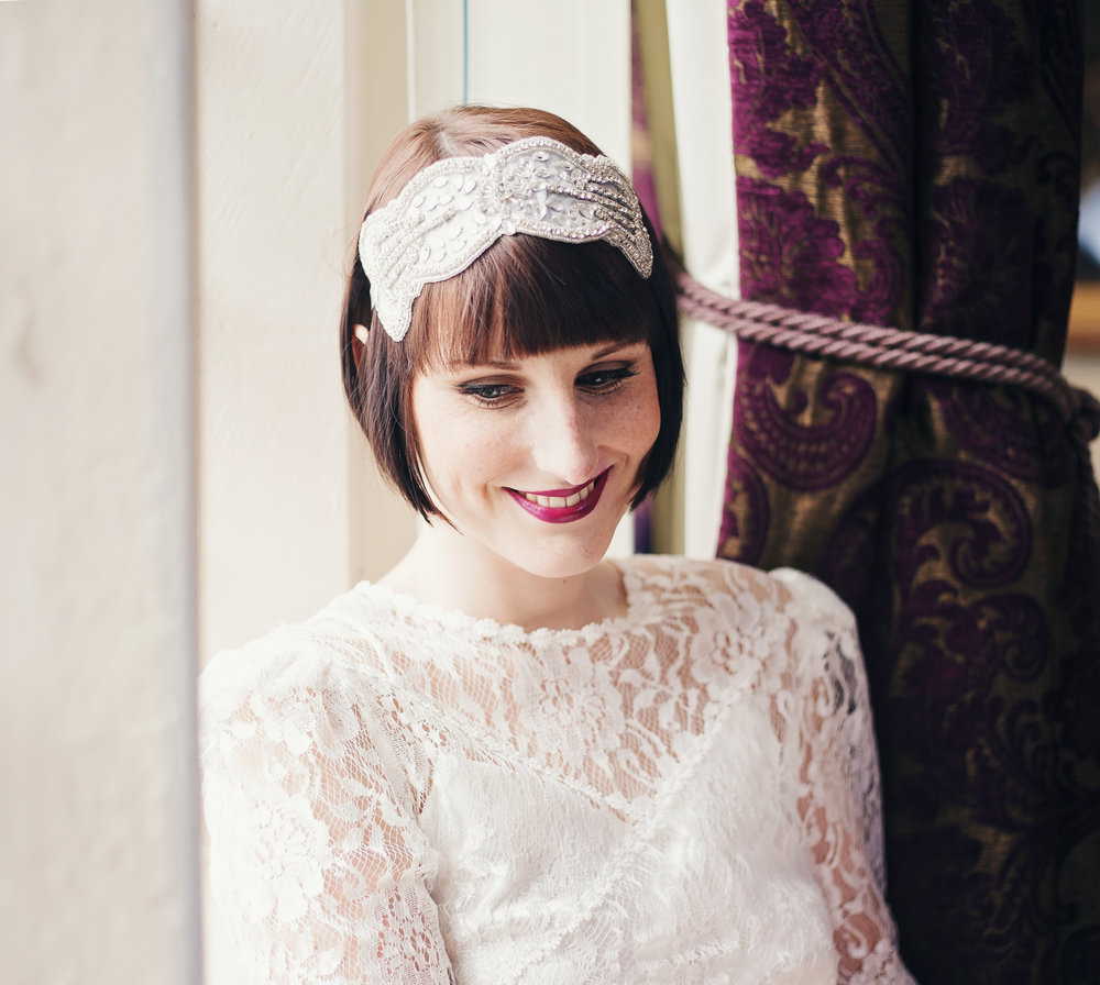 the bride smiling by the window at Haworth Art Gallery- Lancashire wedding photography